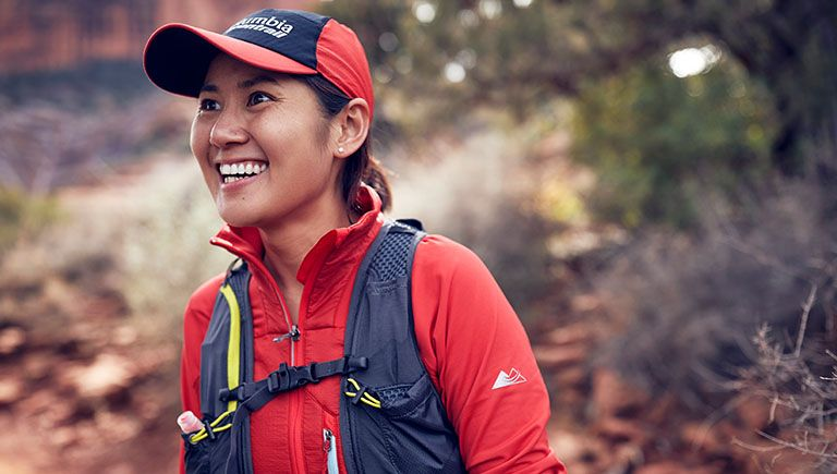 Close-up of a woman in Columbia Montrail gear. Play button linking to How to be a Trail Runner: Gear video.