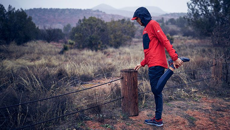 Close-up of a runner stretching in Columbia Montrail gear. Play button linking to How to be a Trail Runner: Nutrition video.
