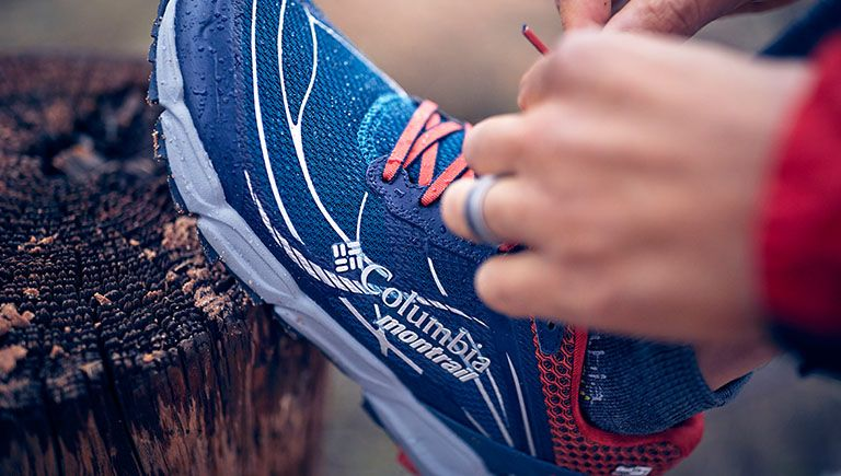 Close-up of a Columbia Montrail shoe. Play button linking to How to be a Trail Runner: Shoes video.