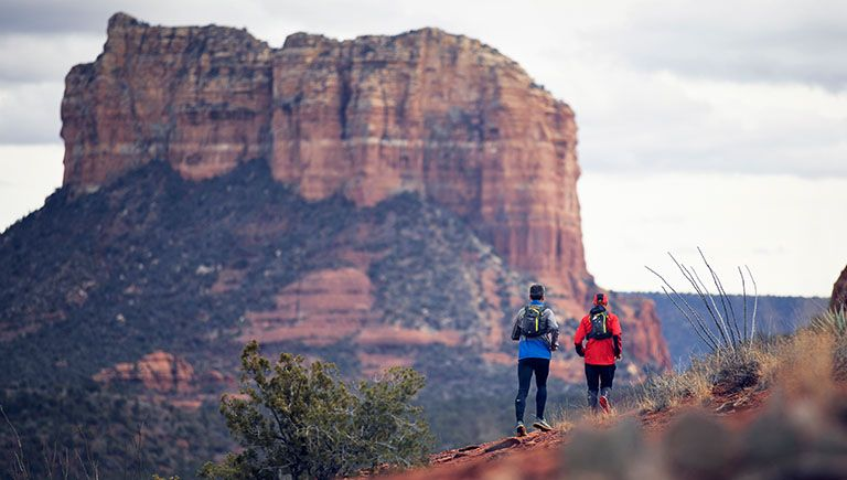 Two people running in Columbia Montrail gear on a rocky trail. Play button linking to How to be a Trail Runner: Training video.