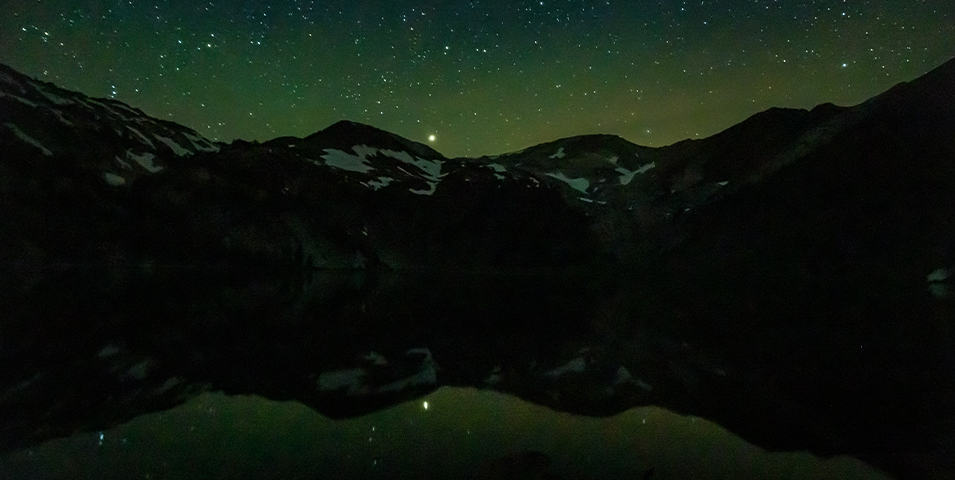 A starry sky above mountains and a lake.