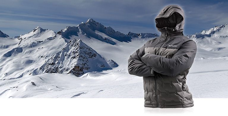 A mens down jacket with its arms crossed against a snowy scene.