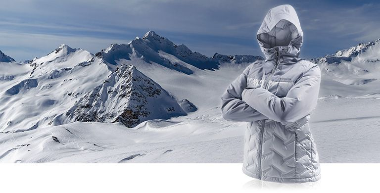 A womens down jacket with its arms crossed against a snowy scene.