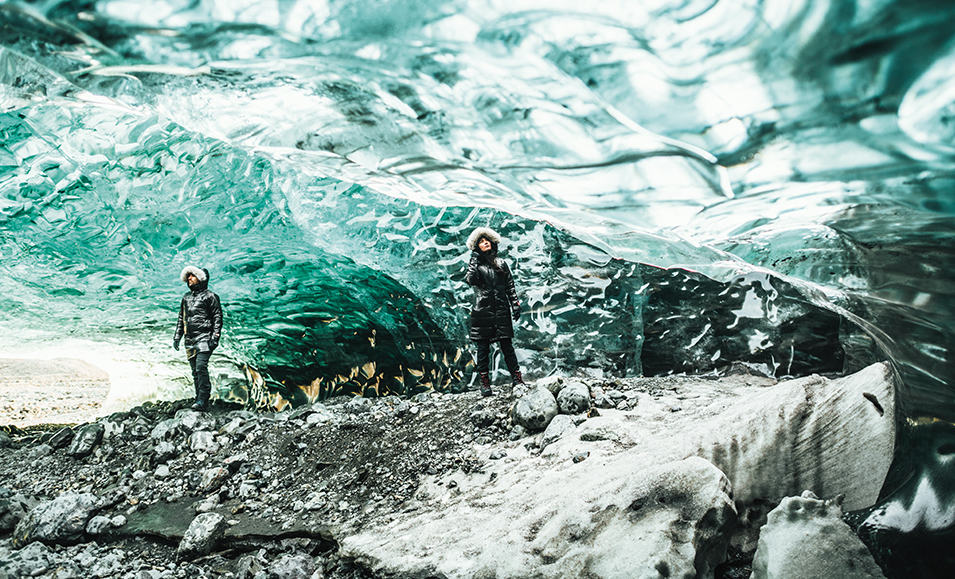 A man and woman exploring ice caves in Black Dot jackets.