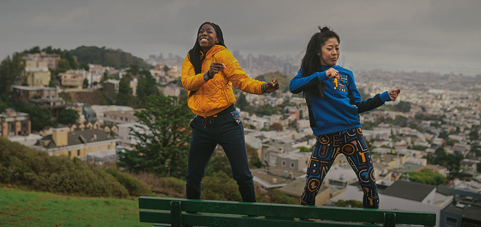 Two women dancing on a park bench overlooking a city.