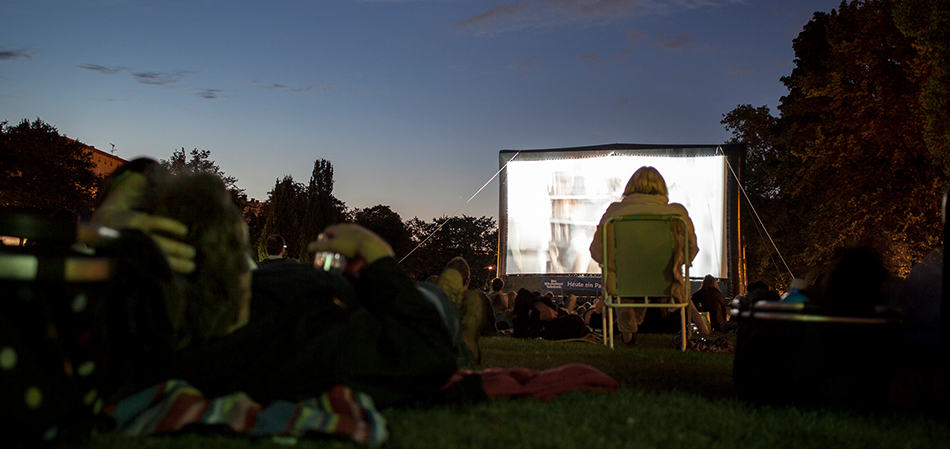 People watching an outdoor movie screen.