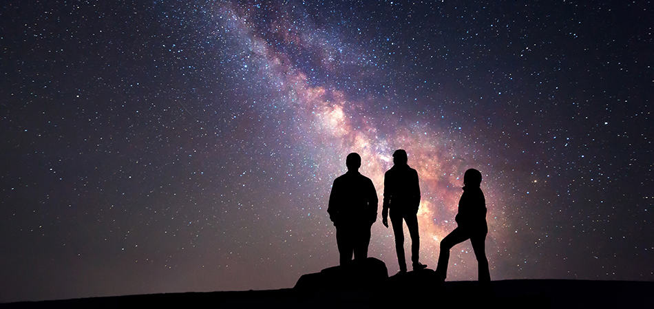 Three people silhouetted against the Milky Way.