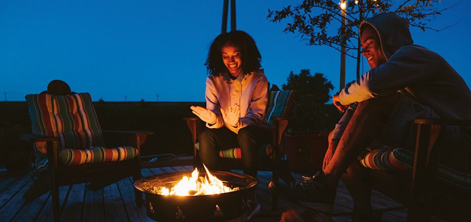 Two friends next to a bonfire.