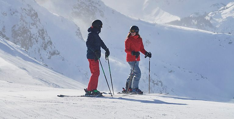 A man and woman on a snowy mountainside in high-performance ski gear.
