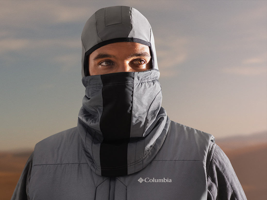 Partial view of man wearing jacket and helmet gaiter.