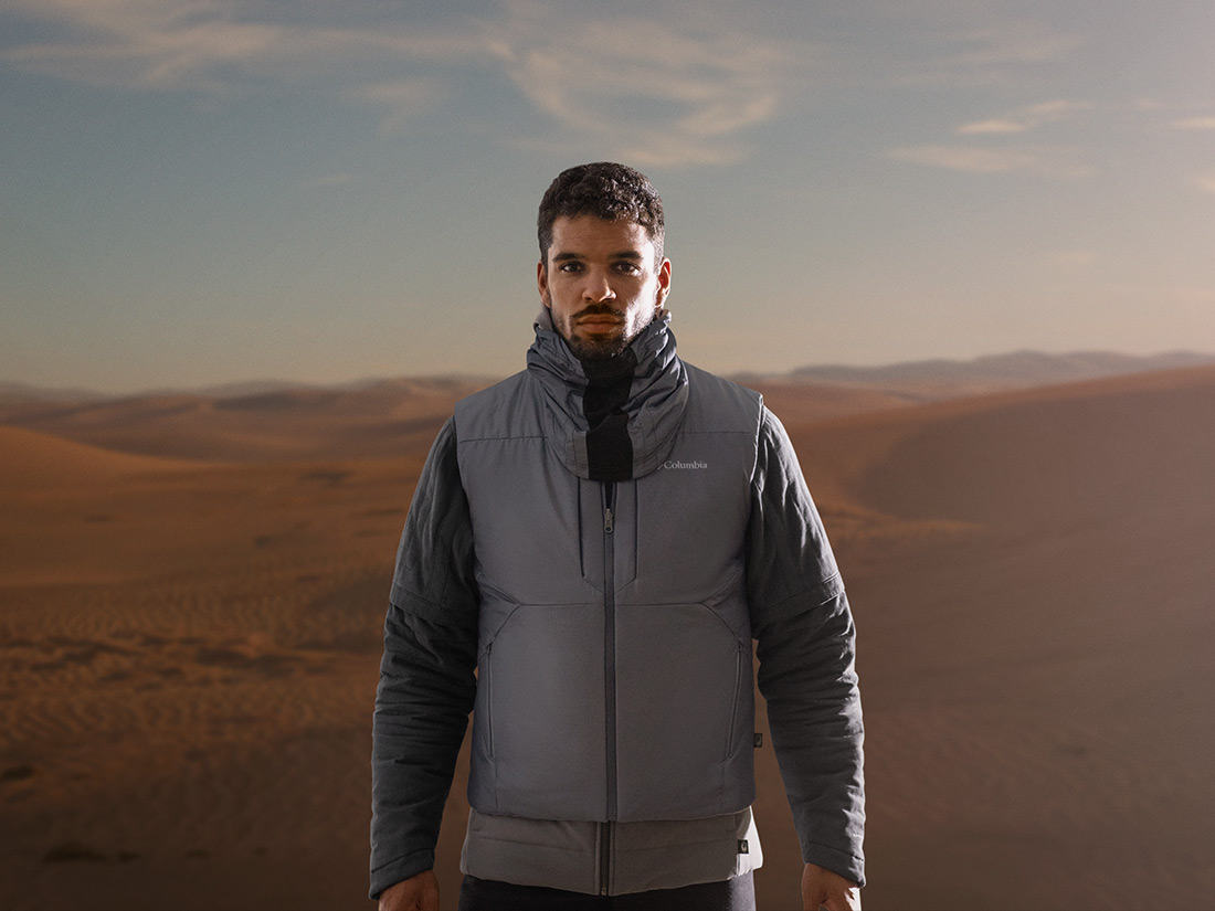 Full view of man wearing the jacket and helmet on desert planet.