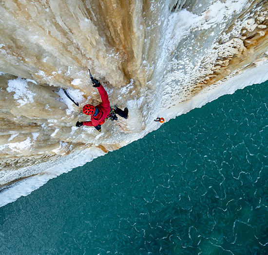 Bird eye view of an ice climber on a route above an icy ocean.