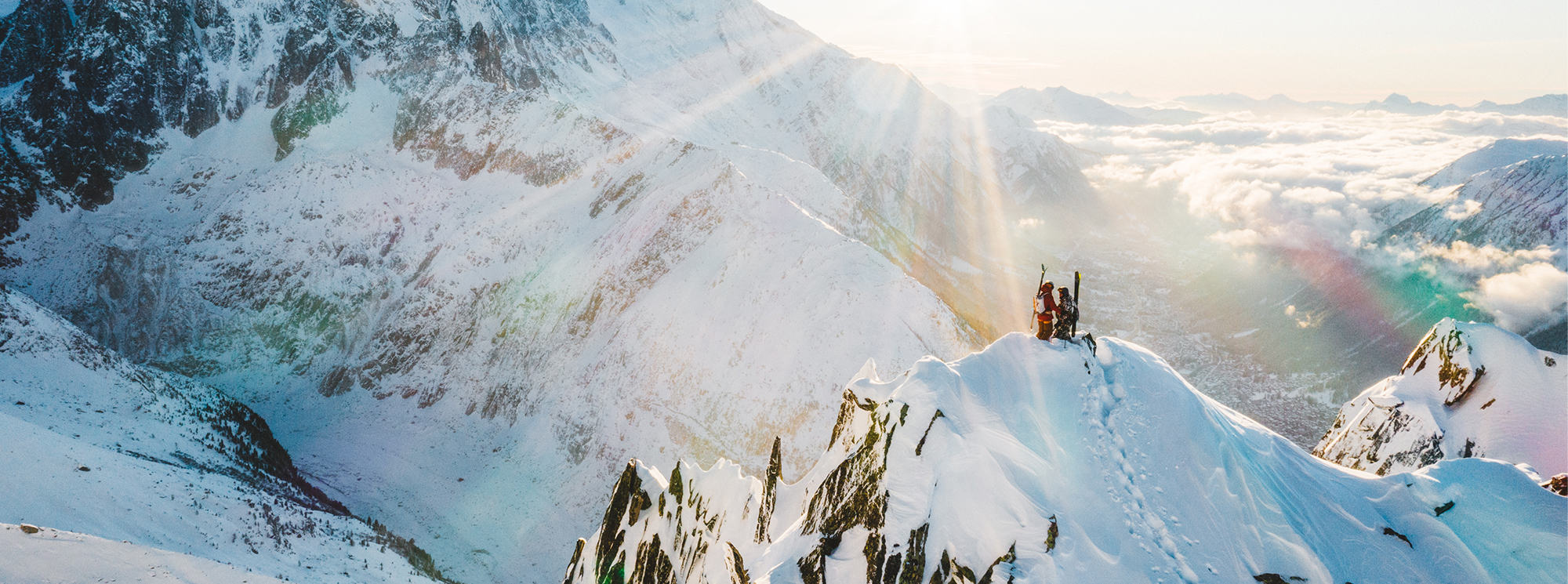 Vivian Bruchez and ski partner, at the top of a skinny ridge in the backcountry, looking down at possible ski lines down at dawn.