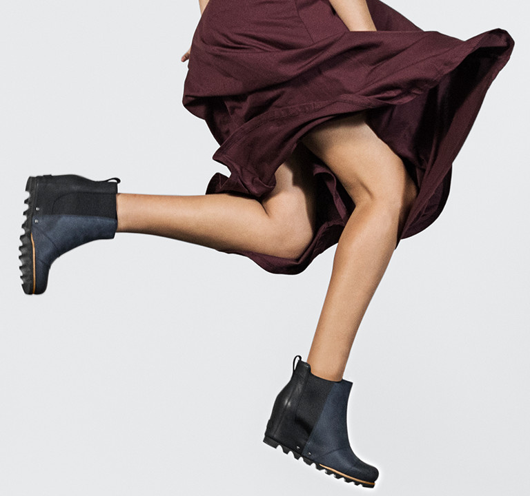 A woman jumping in sneaker duck boots.