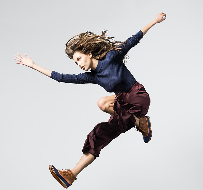A woman jumping in blue wedge boots.