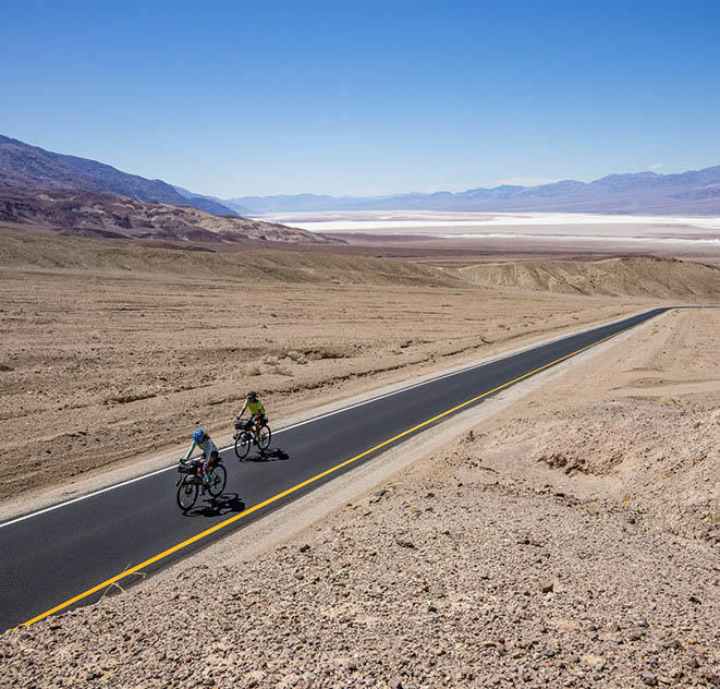 Faith and Mark bicycling on an empty desert road.