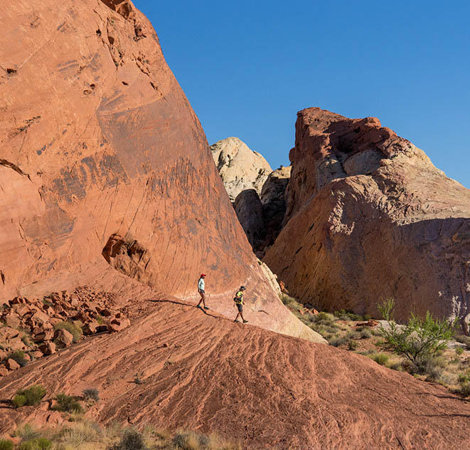 Faith and Mark hike across a red rock formation.
