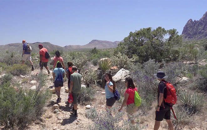 Students hiking through desert with Mark and Faith.