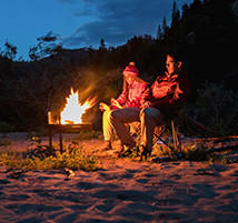 Faith and Mark sit by a campfire on the banks of the river.