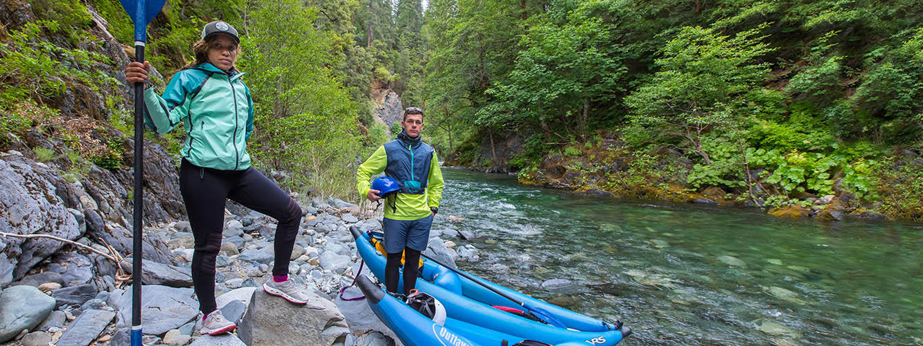 Video of Klamath River journey; Image of Faith and Mark standing beside their kayaks on the riverbank.