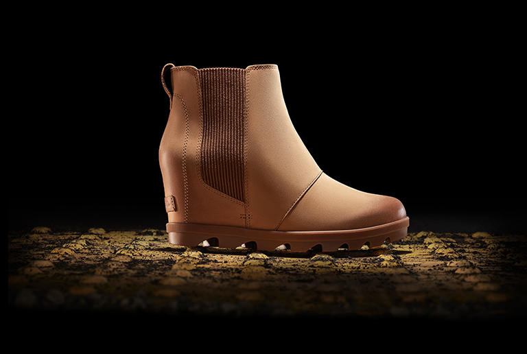 A camel brown Joan Wedge Chelsea boot in an urban setting
