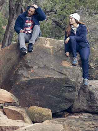 A boy and a girl sitting on a rock wearing fall clothing.