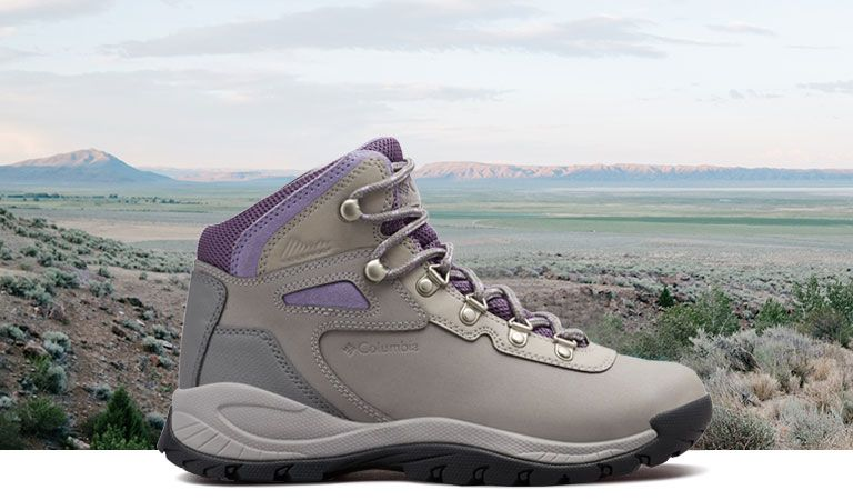 A grey and purple Newton Ridge boot in front of a beautiful plains landscape.