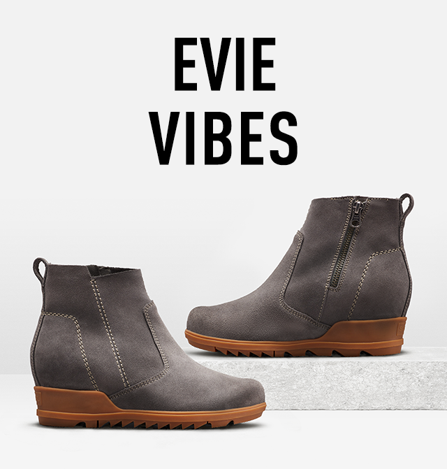 EVIE VIBES, A pair of Evie booties styled on a slab of concrete with white background
