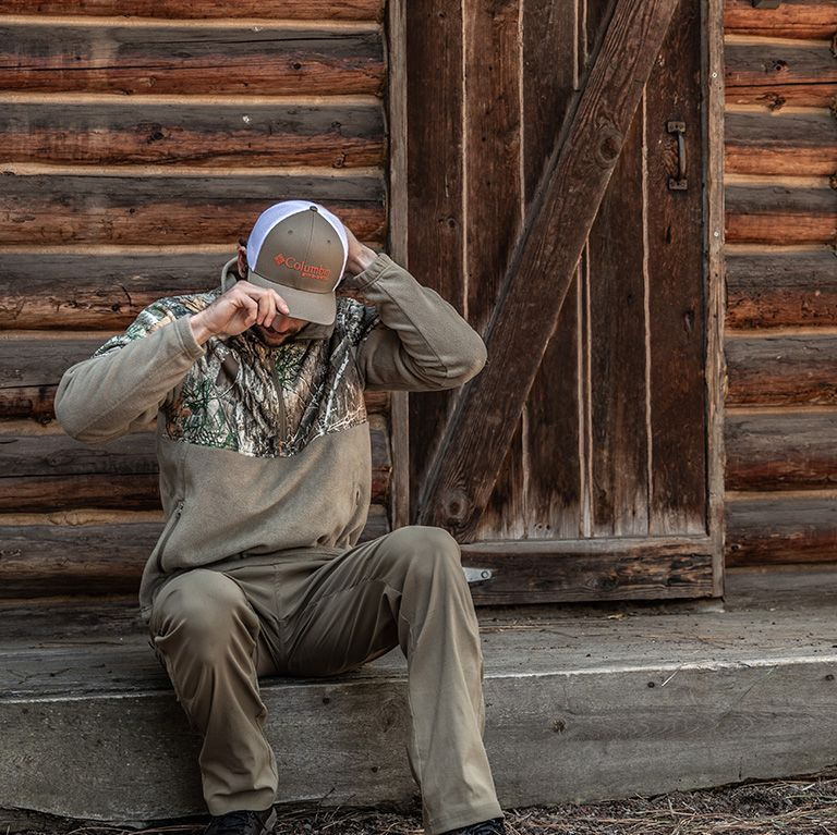 A man outside a cabin.