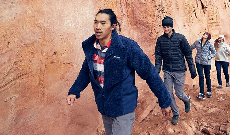 A group of people wearing new fall arrivals hike at the base of a red-rock face.