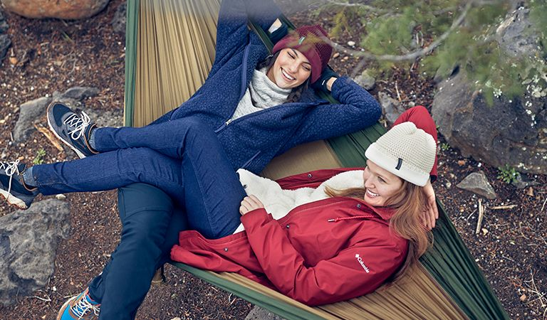 Two women on a hammock in fall gear.