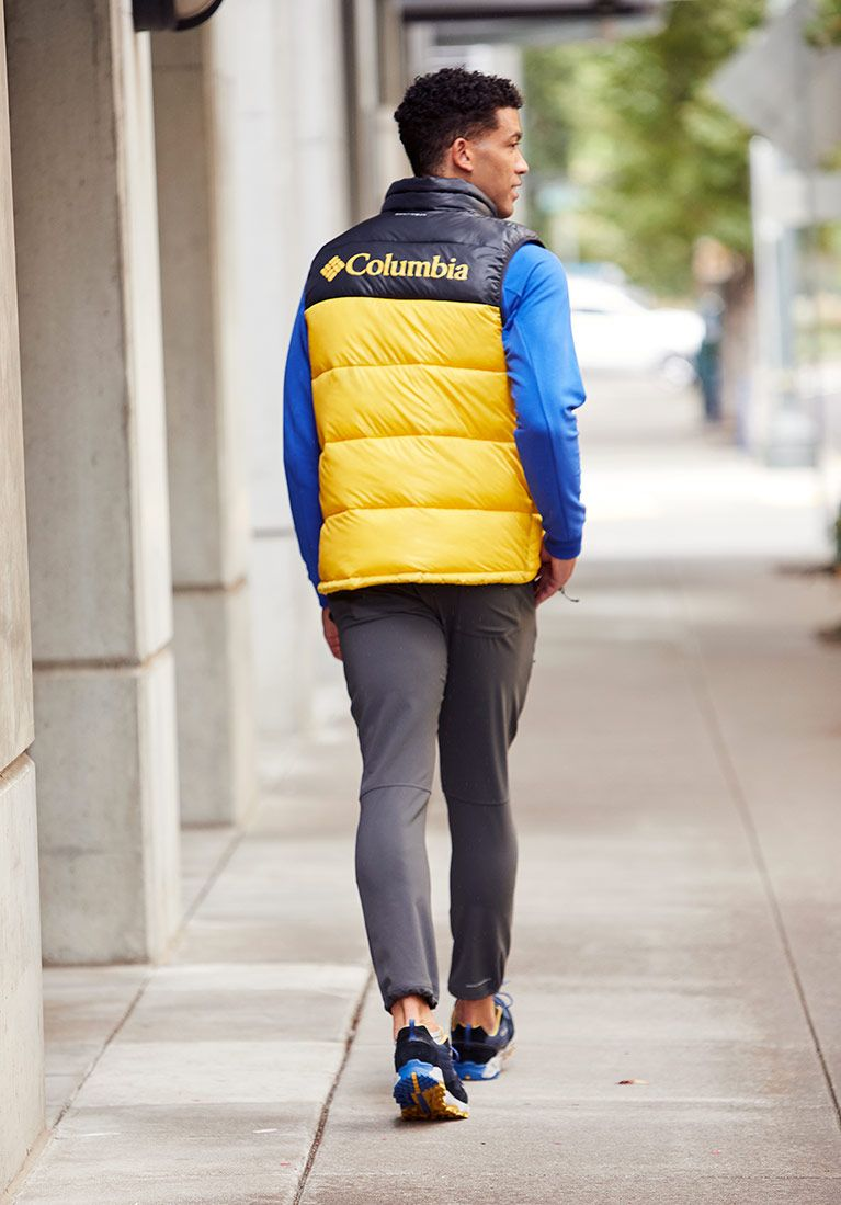 Head to toe look Man in yellow and black down vest, blue shirt, gray pants, sneakers.