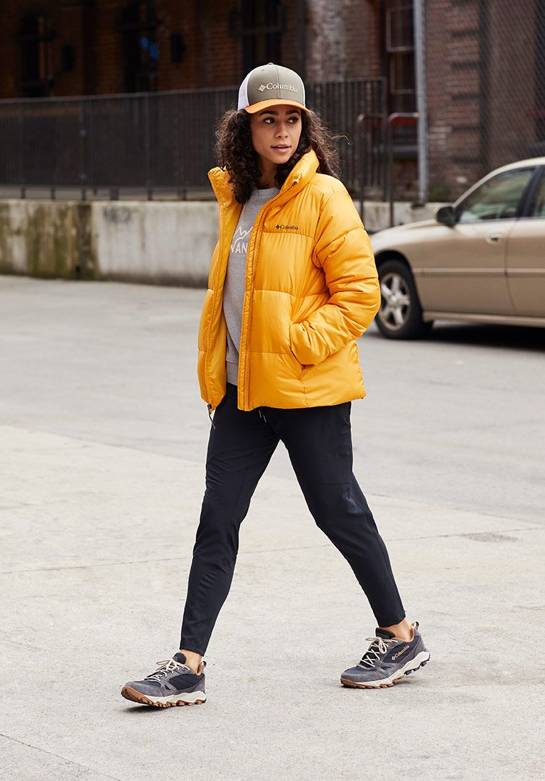 Head to toe womens look Cap, grey crew, yellow puffy, black joggers, sneakers.