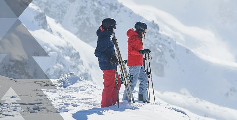 Two people about to ski down a slope