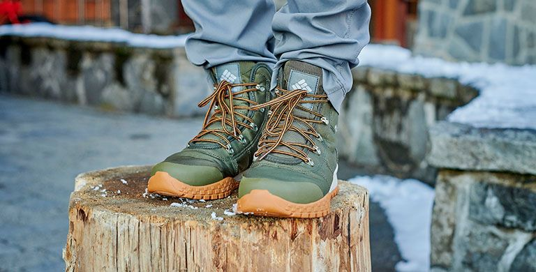 A pair of rugged winter boots on a snowy log.