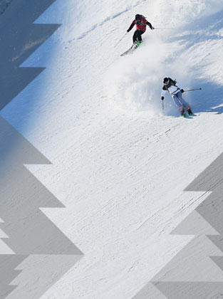 Two skiers carving turns down a pristine hill.