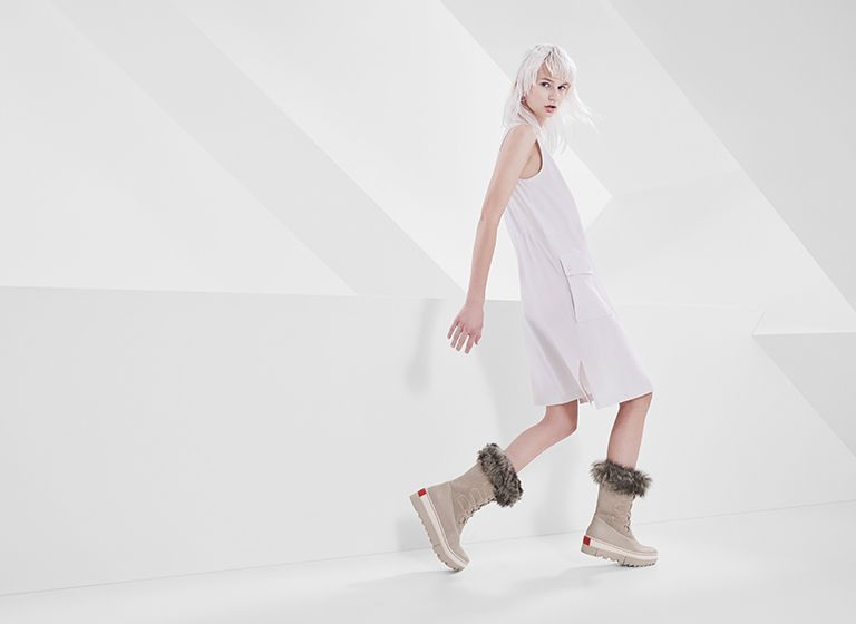 Woman posing wearing pair of Joan NEXT boots with futuristic background