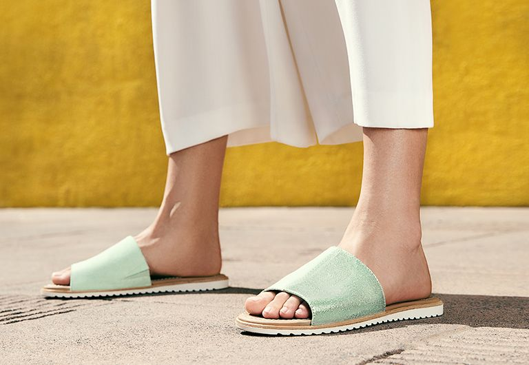 Woman wearing mint colored SOREL sandals in colorful city setting