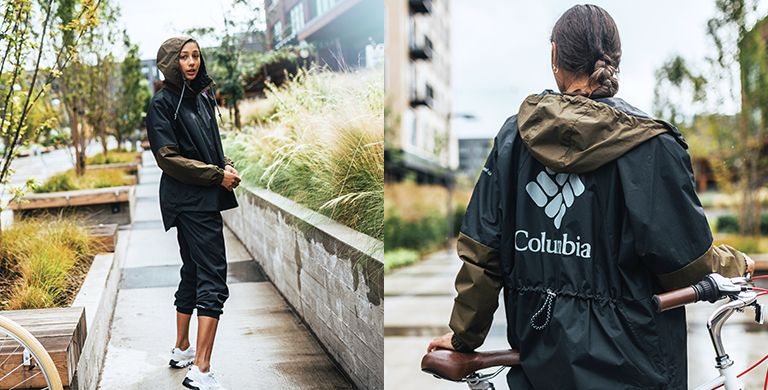 A woman wearing  a jacket with an oversized Columbia logo.