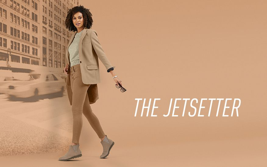 The JETSETTER, woman holding sunglasses wearing SOREL boots with beige background