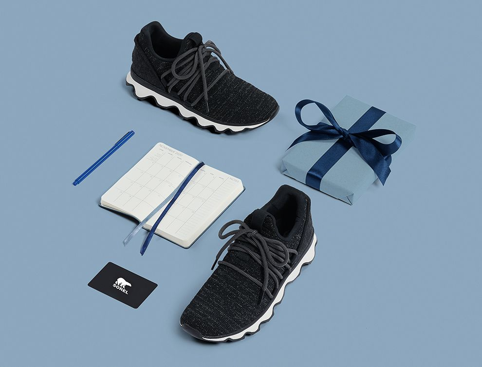A pair of Kinetic Sneaks, agenda, and gift on blue background