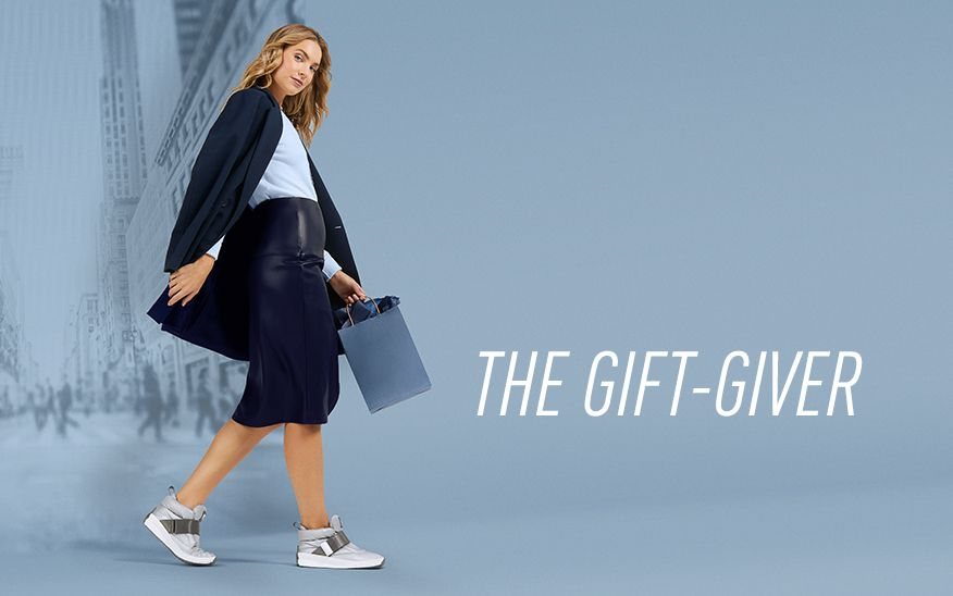 THE GIFT-GIVER, woman holding shopping bag wearing SORELs on blue background