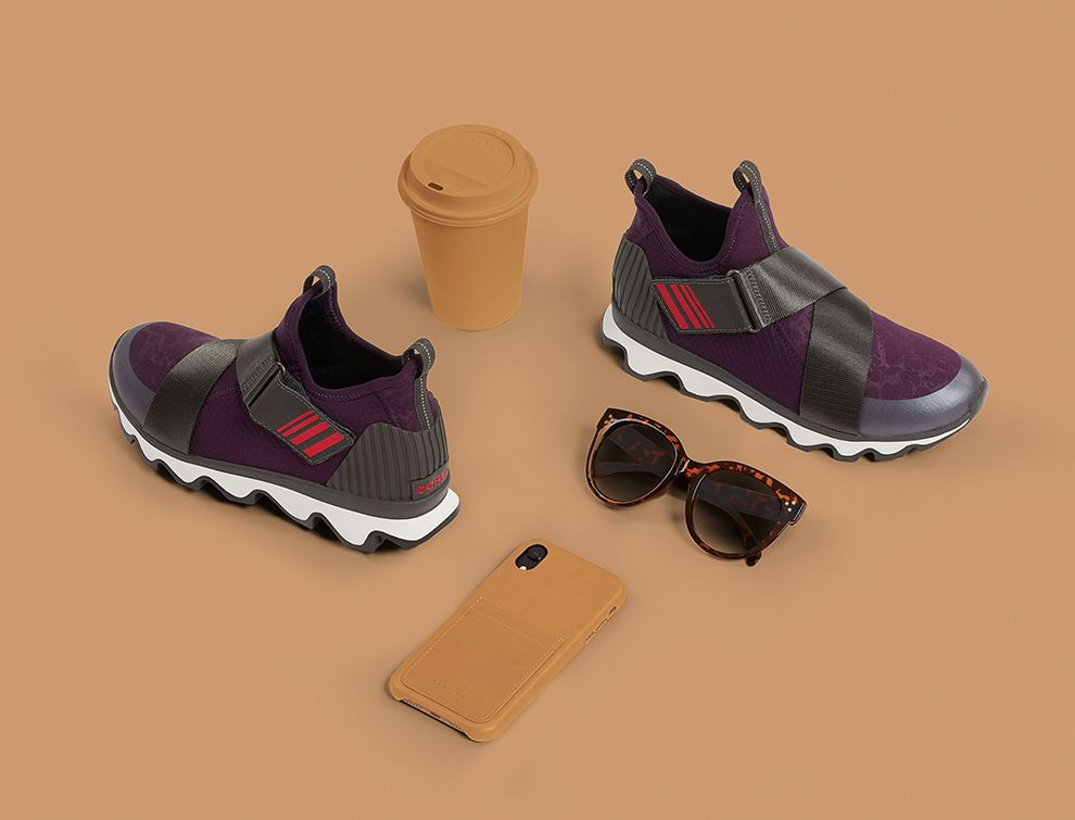A pair of purple Kinetic Sneaks with a phone and sunglasses on beige background