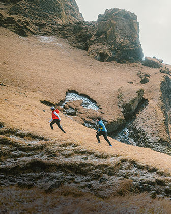 Two people hiking up a steep hillside.