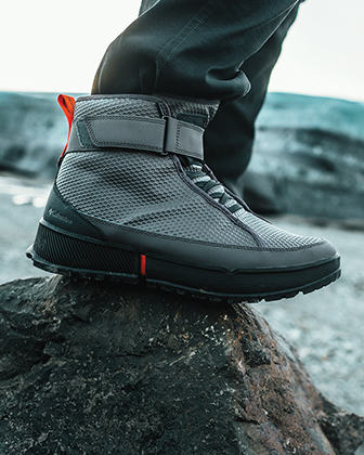 A close up of a boot atop a rock in a cold landscape.