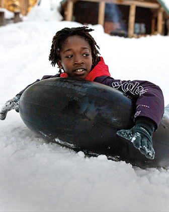 A kid in warm gear playing in the snow with an inner tube.