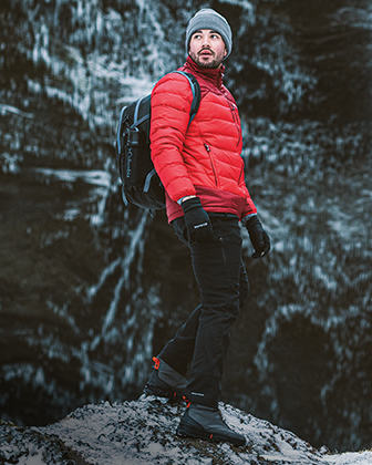 A man in warm gear hiking a cold rocky landscape.