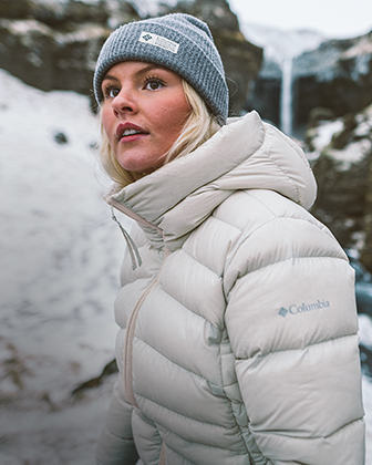 A woman in a warm puffy jacket hiking a snowy landscape.