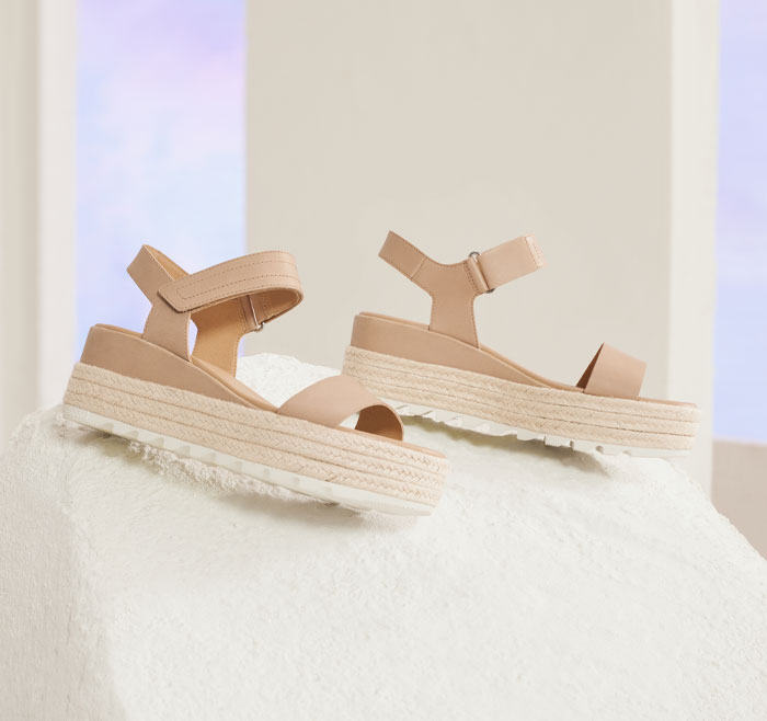 A pair of Cameron Flatform sandals on an beige background