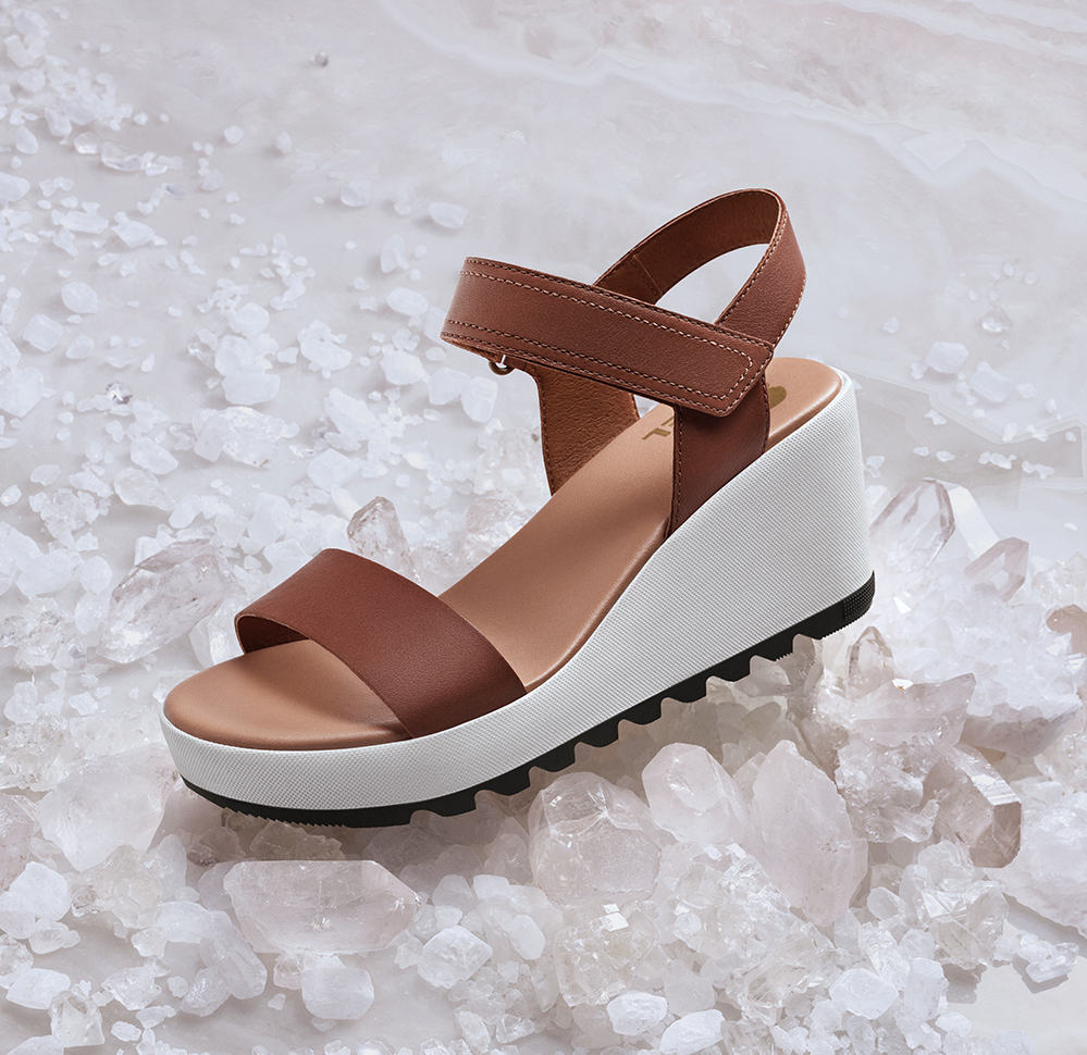 A Cameron Wedge sandal surrounded by white crystals.